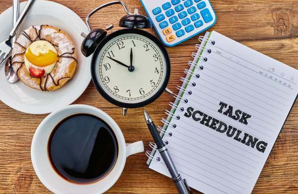 task scheduling written on a notebook beside an alarm clock, coffee and pastries