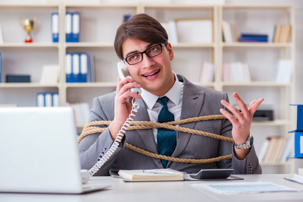 officce employee tied up in a 9-to-5 work setup
